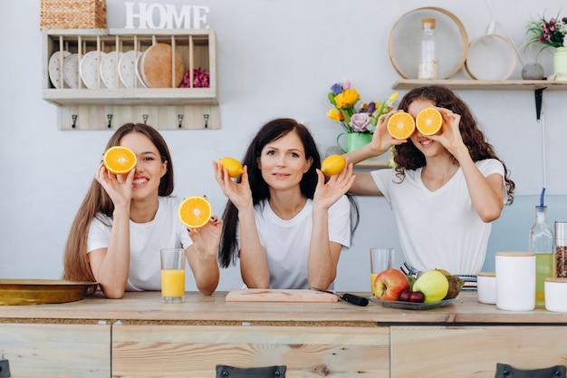 Meninas muito encantadoras segurando laranjas e limões