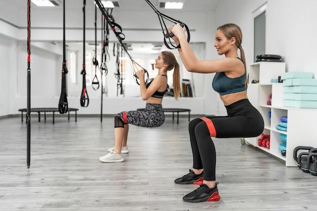 Meninas muito esportivas treinando em uma academia com equipamento trx moderno e realizando agachamentos com elástico durante exercícios eficazes de corpo inteiro
