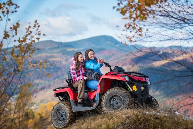 Meninas na bicicleta quad vermelho na colina faz selfie no telefone