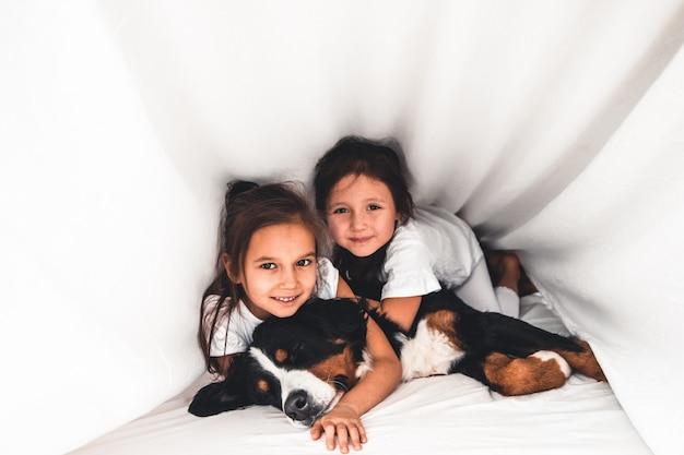 Meninas na cama com cachorro bernese mountain dog, amizade