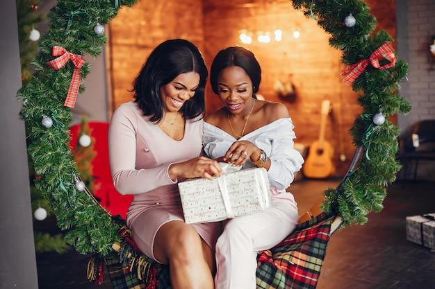 Meninas negras elegantes nas decorações de natal