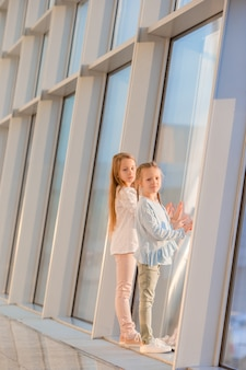 Meninas no aeroporto perto da grande janela enquanto espera pelo embarque