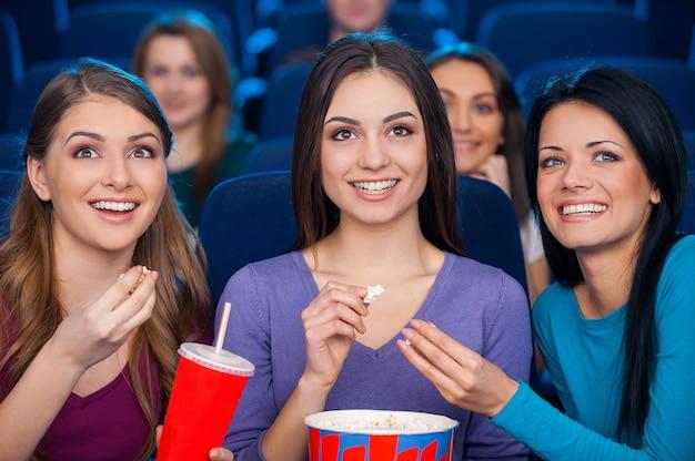 Meninas no cinema. mulheres jovens felizes comendo pipoca e bebendo refrigerante enquanto assistem a um filme no cinema juntas