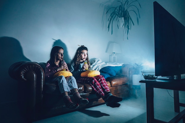 Meninas no quarto escuro assistindo filme