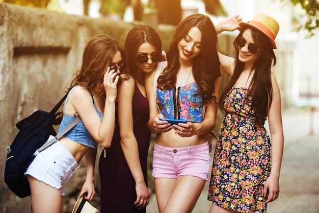 Meninas no verão que olha uma fotos em um smartphone