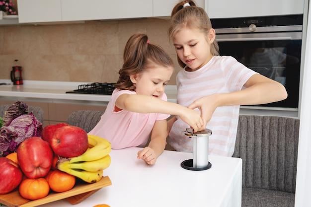 Meninas, olhando para a tomada elétrica na mesa da cozinha moderna