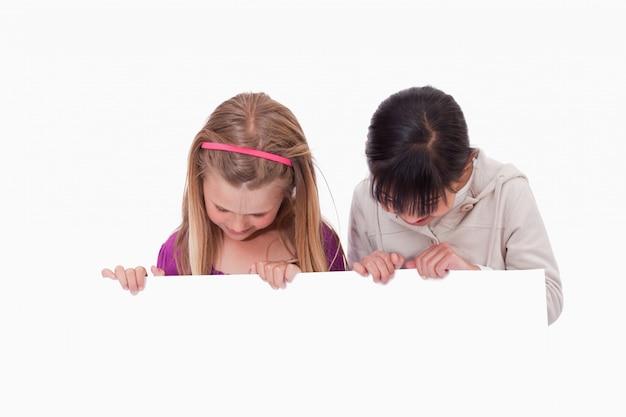 Meninas olhando para um painel em branco