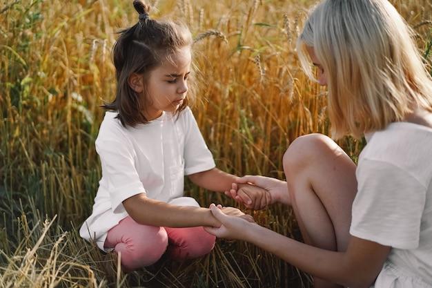 Meninas orando e de mãos dadas em um campo de trigo. ore para que deus se apóie juntos.