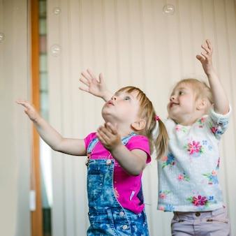 Meninas pegando bolhas de sabão no quarto