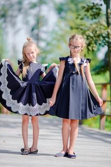 Meninas pequenas adoráveis da escola fora no dia morno de setembro. de volta à escola.