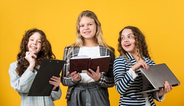 Meninas pequenas com livro de pasta de escritório e laptop. pequenas empresárias. infância feliz. crianças usam jaqueta. trabalhar com notebook. estudante tem dever de casa de papelada online. de volta à escola.