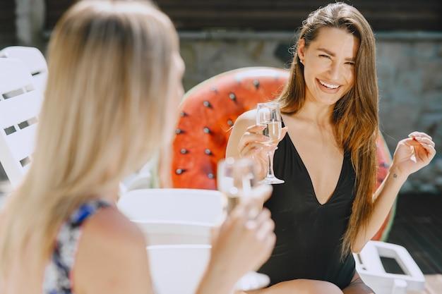 Meninas perto de uma piscina. amigos em um maiô elegante. senhoras em férias de verão.