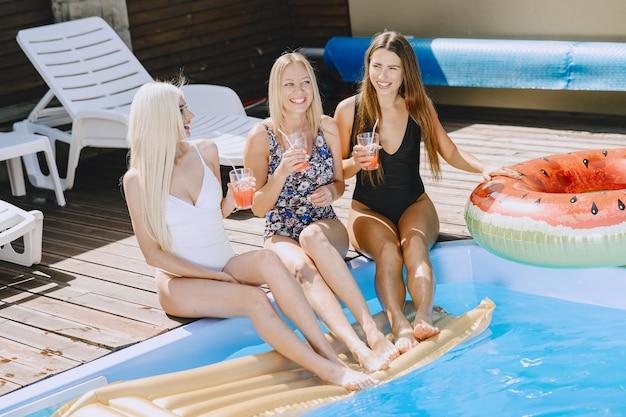 Meninas perto de uma piscina. mulheres em trajes de banho elegantes. senhoras em férias de verão.