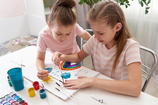 Meninas pintando nas unhas com aquarela se divertindo