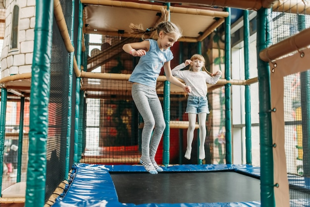 Meninas pulando na cama elástica, centro de jogos infantis