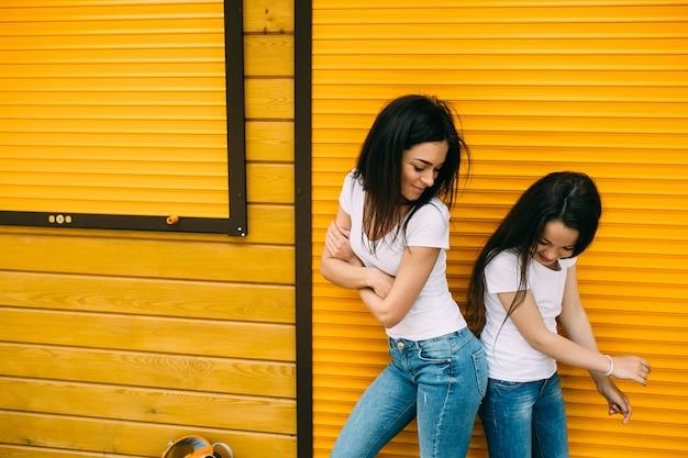 Meninas que batem quadris em pé contra a parede de laranja
