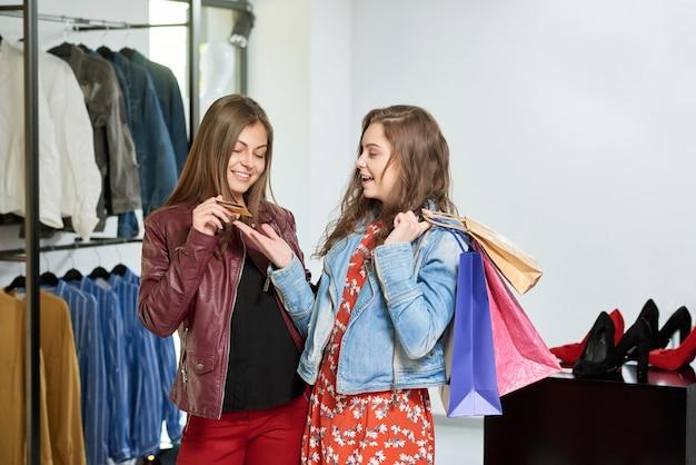 Meninas que compram a roupa durante a compra na alameda.