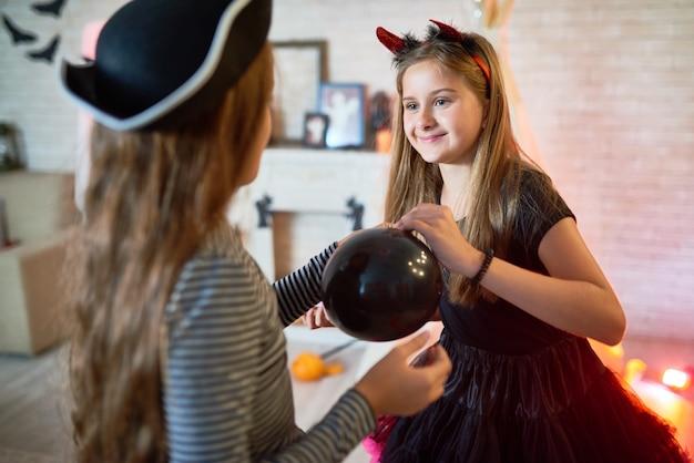 Meninas que decoram o quarto para a festa de halloween