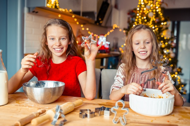 Meninas que fazem a casa de gengibre de natal na lareira na sala de estar decorada.