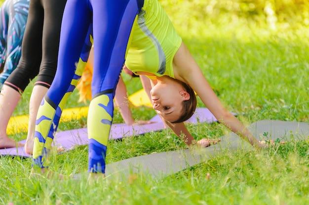 Meninas que levantam a ioga fora na floresta na manhã