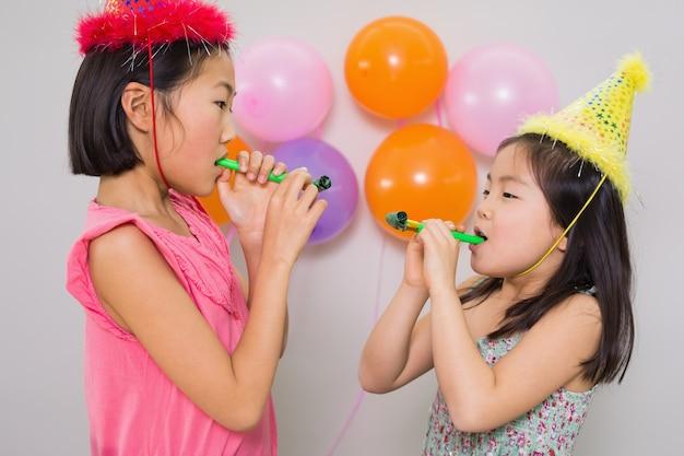 Meninas que sopram noisemakers em uma festa de aniversário