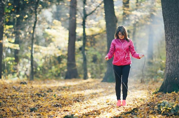 Meninas que treinam e ouvem música na floresta da manhã