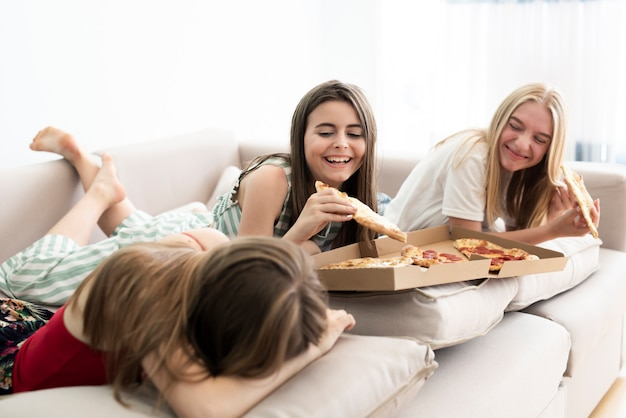 Meninas relaxando em casa e comendo pizza
