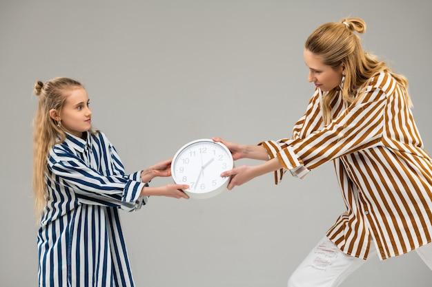 Meninas resolutas de cabelos claros em camisas listradas competindo pelo relógio branco de sempre usando todas as forças