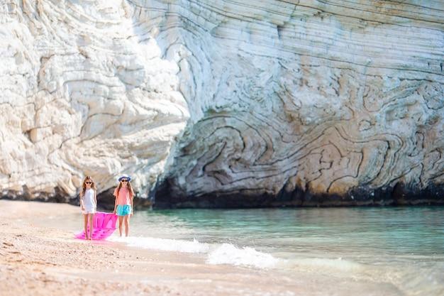 Meninas se divertindo na praia tropical durante as férias de verão tocando juntos