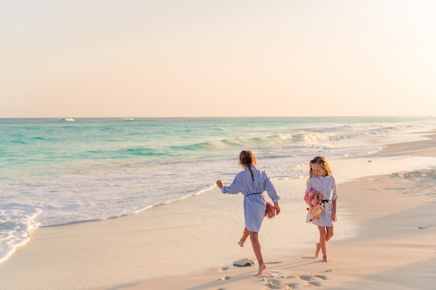 Meninas se divertindo na praia tropical tocando juntos em águas rasas