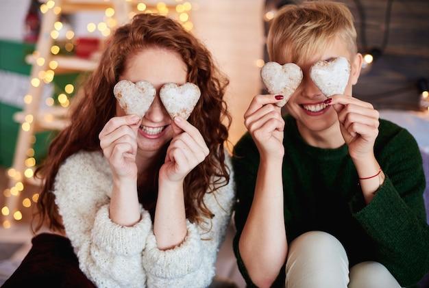 Meninas segurando biscoitos de gengibre em forma de coração