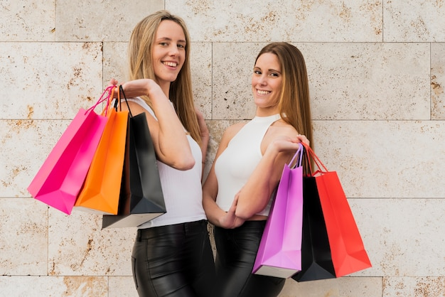 Meninas segurando sacolas de compras, olhando para a câmera