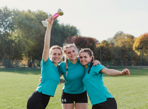 Meninas, segurando um troféu de esporte e olhando para o fotógrafo