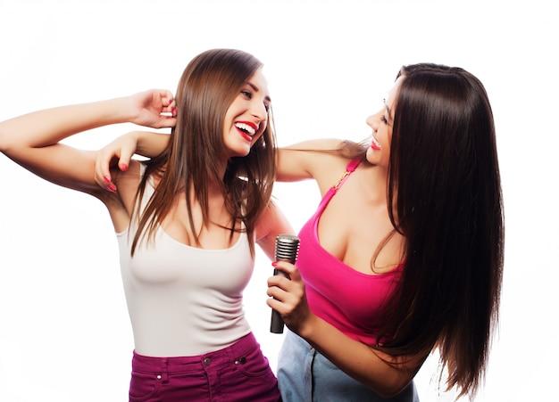 Meninas sensuais cantando com microfone