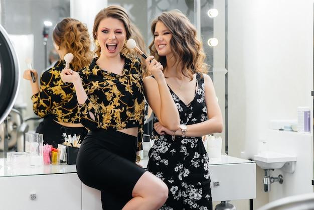 Meninas sensuais se divertem e se arrumam para uma festa em frente ao espelho. moda e beleza.
