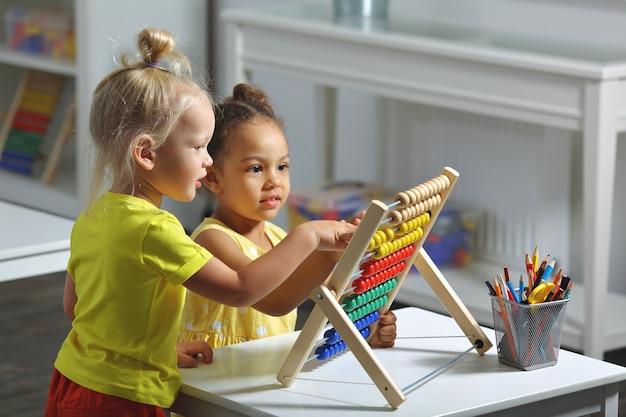 Meninas sentadas juntas à mesa e contando com o ábaco com um sorriso.