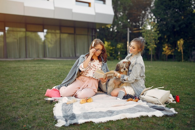 Meninas, sentado em um cobertor em um parque de verão