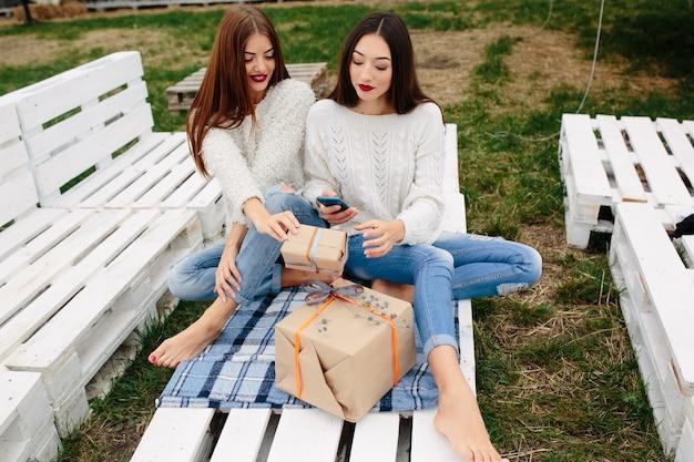 Meninas sentado em um pallet de madeira branca com um presente olhando para um celular