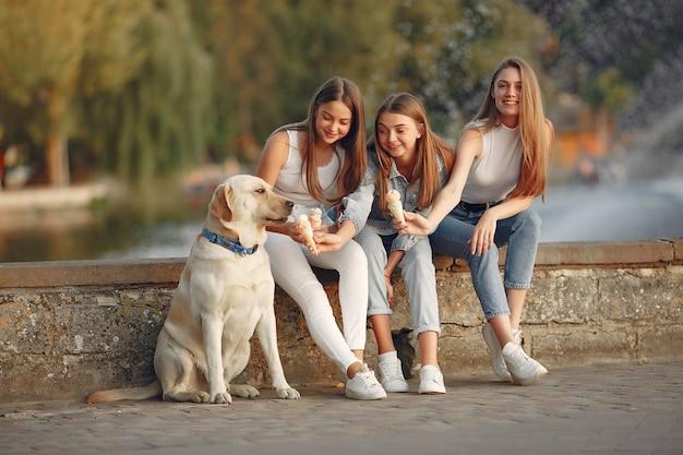 Meninas, sentado em uma cidade de primavera com cachorro fofo