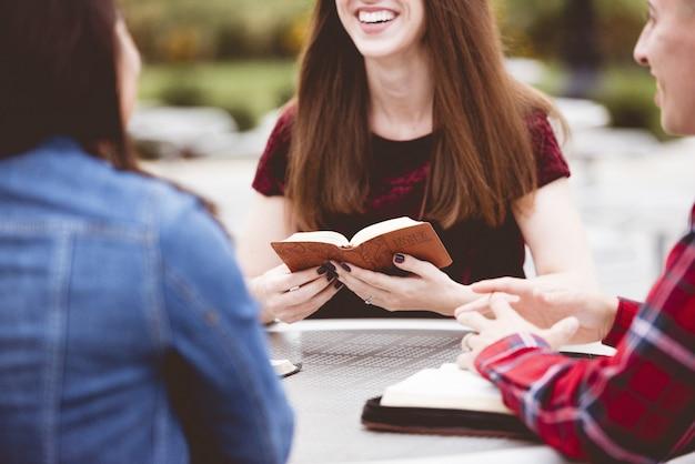 Meninas, sentados ao redor de uma mesa e lendo um livro com um fundo desfocado