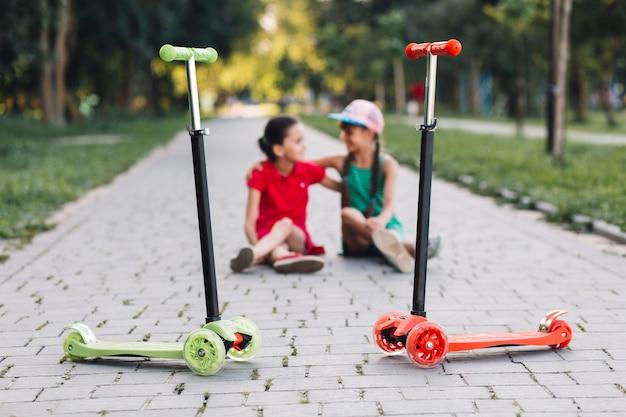 Meninas, sentando, atrás de, empurre scooters, ligado, passagem, parque