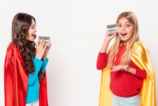 Meninas sorridentes com traje de herói e walkie-talkie