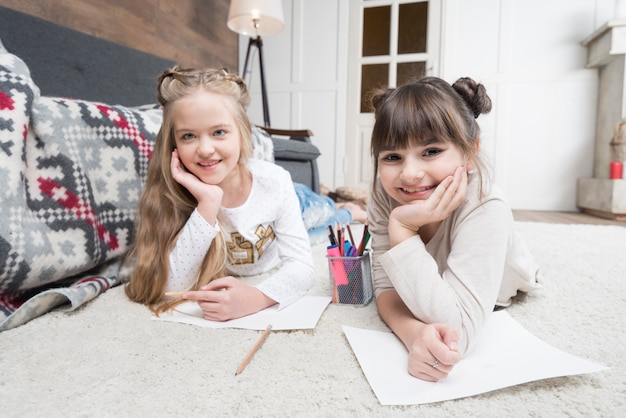 Meninas sorridentes fazendo lição de casa