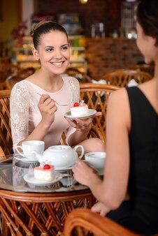 Meninas sorrindo e tomando café juntos.