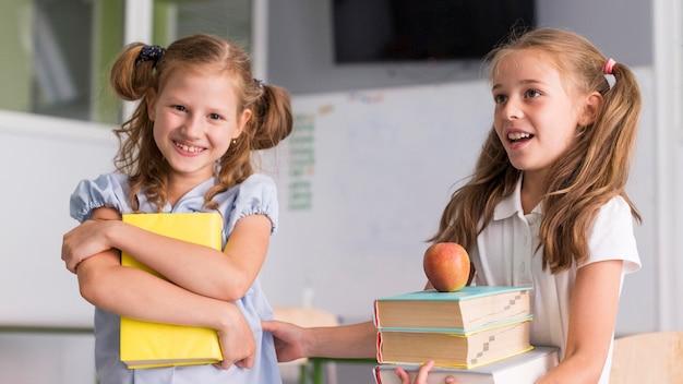 Meninas sorrindo enquanto seguram seus livros