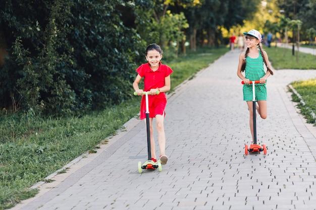 Meninas sorrindo, montando, ligado, empurre scooter, sobre, passagem, parque