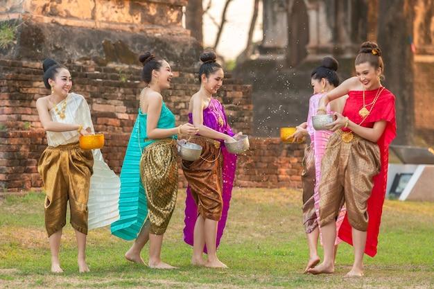Meninas tailandesas e meninas de laos, salpicos de água durante festival festival songkran