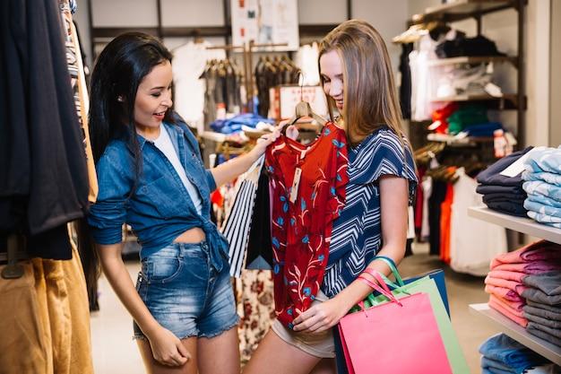 Meninas tentando roupas na loja
