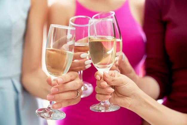 Meninas, tilintar de copos com champanhe.