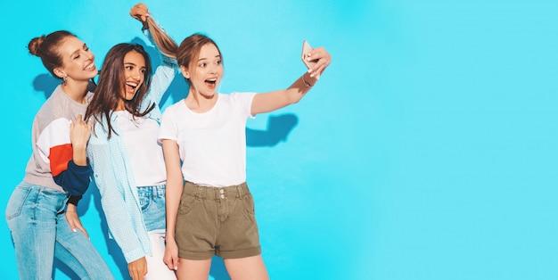 Meninas, tirando fotos de auto-retrato de selfie no smartphone. modelos posando perto de parede azul no estúdio, fêmea, mostrando emoções de rosto positivo